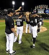 CHICAGO - JULY 09:  Andruw Jones #25 high fives Jake Peavy #44 of the Chicago White Sox after the game against the Kansas City Royals on July 9, 2010 at U.S. Cellular Field in Chicago, Illinois.  Jones had three hits in the game.  The White Sox defeated the Royals 8-2.  (Photo by Ron Vesely)