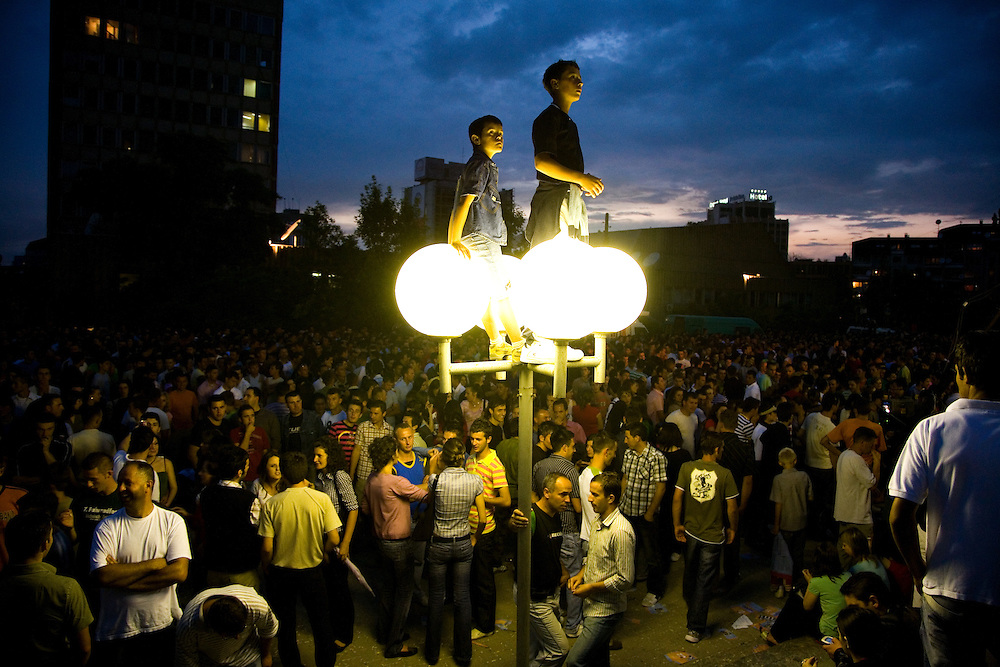 A young fan climbed a light pole outside the National Library of Kosovo in Pristina for a better view during a large public concert on a June evening, which attracted people from around Kosovo to the capitol. .