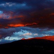 SHOT 8/16/11 7:55:00 PM - A panoramic view of Bald Mountain as the last light of the day hits the highest point and dramatic clouds pass overhead. Bald Mountain is the highest point of a 6 mile long ridgeline to the southeast of Breckenridge. This ridgeline runs northwest to southeast and rises above 12000 ft. Half way along the length of it, a 12159 ft saddle divides the ridgeline into two sections: the southeast section is known as Boreas Mountain (13082 ft) and the northwest section is Bald Mountain. Near its northwestern end, the crest of the ridgeline exceeds 13400 ft over an area 0.8 miles long. The USGS map identifies three high points along the length of this area. Southeast to northwest, these include: Point 13679 ft, Point 13634 ft and Point 13684 ft (the official summit of Bald Mountain). Established in 1859, the historic town of Breckenridge is a home rule municipality that is the county seat of Summit County, Colorado, United States. As of the 2010 Census, the town had a population of 4,540. The town also has many part-time residents, as many people have vacation homes in the area. Breckenridge is also a popular ski resort during the winter months and summer in Breckenridge attracts outdoor enthusiasts with hiking trails, wildflowers, fly-fishing in the Blue River and mountain biking. (Photo by Marc Piscotty / © 2011)