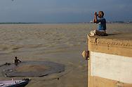 Hindu man praying at Rana Ghat  by the Ganges river in Varanasi, India.