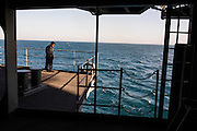 A crew member has a rare moment of solitude on the fantail (the rear of the ship) <br /> <br /> Aboard the USS Harry S. Truman operating in the Persian Gulf. February 25, 2016.<br /> <br /> Matt Lutton / Boreal Collective for Mashable