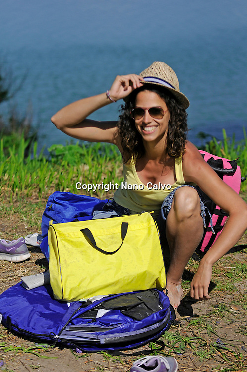 Young woman finishes packing up in Cies Islands (Islas Cíes) camping, Pontevedra, Galicia, Spain