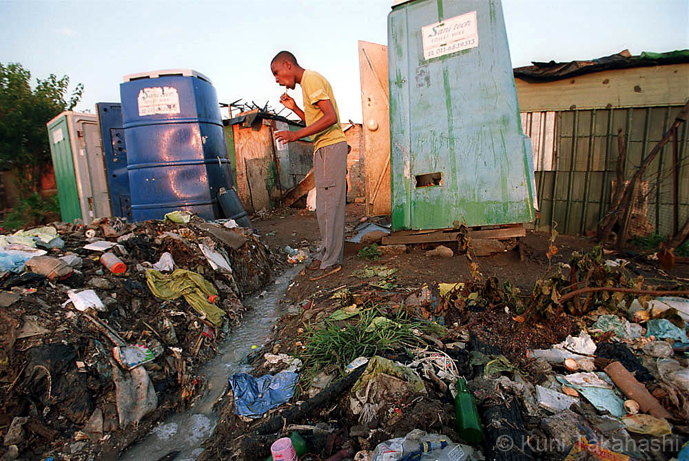 Man brushes teeth in squatter camp near Johannesburg, South Africa in April, 2002.