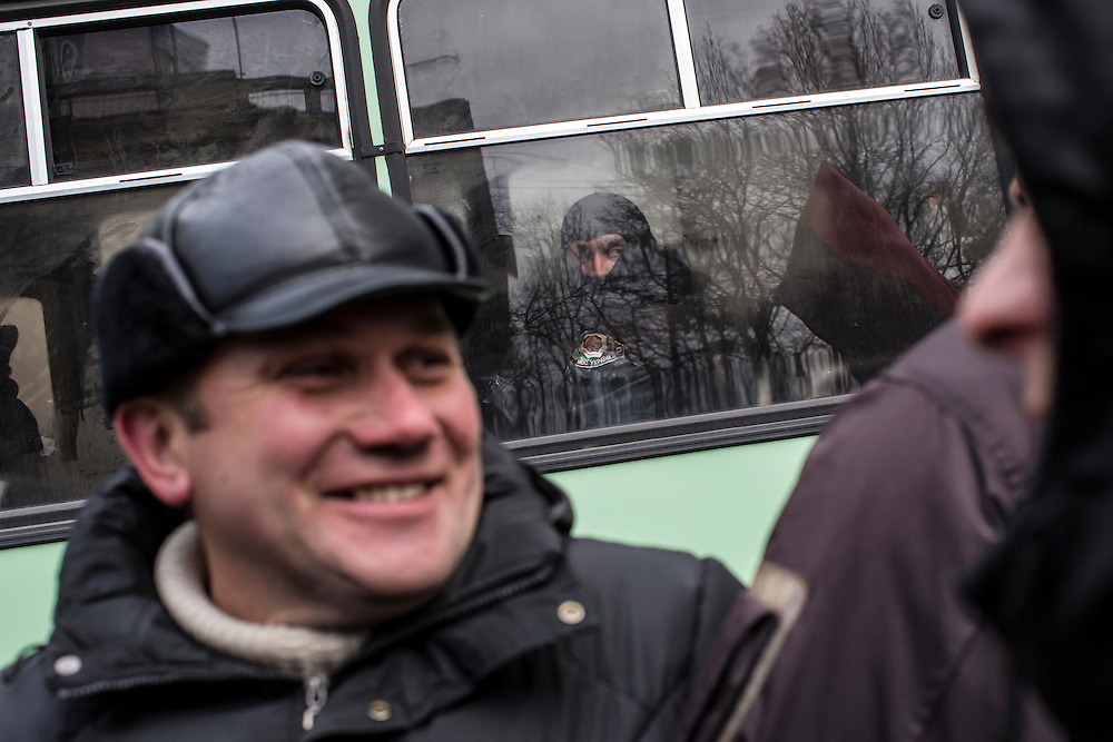 KIEV, UKRAINE - DECEMBER 4: Police watch from inside a bus used to block a street as anti-government protesters rally on December 4, 2013 in Kiev, Ukraine. Thousands of people have been protesting against the government since a decision by Ukrainian president Viktor Yanukovych to suspend a trade and partnership agreement with the European Union in favor of incentives from Russia. (Photo by Brendan Hoffman/Getty Images) *** Local Caption ***