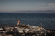 A Turkish smuggler is seen back to shore after evading attempts by volunteers and locals to capture him after he tried to swim back to Turkey (background coast). He came along refugees on Pharos beach near Molyvos with intention to return to Turkey with the boat. Has he failed to keep his boat, he jumps to the sea while ripping off his clothes to swim back to his country. He shortly after returned to the beach (photo) where he desperately tried to seize an incoming migrant dinghy but as he was becoming too nervous volunteers jumped him andkept him restrained <br /> until Greek Coast Guard picked him to detention. Refugees from Afghanistan and Syria arrive in boats on the shores of Lesbos near Molivos, Greece on 11<br /> November, 2015. Lesbos, the Greek vacation island in the Aegean Sea between Turkey and Greece, faces massive refugee flows from the Middle East countries.