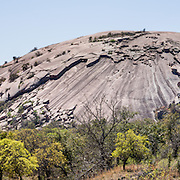 """Explore a large pink granite dome at Enchanted Rock State Natural Area, between Fredericksburg and Llano, Texas, USA. Enchanted Rock is a fascinating exfoliation dome (with layers like an onion), rising 425 feet (130 m) above its surroundings to elevation of 1825 feet (556 m) above sea level, in the Llano Uplift. Geologically, the exposed rock (monadnock or inselberg, """"island mountain"""") is part of a pluton (bubble of rock slowly crystallized from magma) within the billion-year-old igneous batholith, Town Mountain Granite (covering 62 square miles mostly underground), which intruded from a deep pool of hot magma 7 miles upwards into the older metamorphic Packsaddle Schist. The overlying sedimentary rock (Cretaceous Edwards limestone) eroded away to expose the prominent domes seen today: Enchanted Rock, Little Rock, Turkey Peak, Freshman Mountain, and Buzzard's Roost. This panorama was stitched from 3 overlapping photos."""
