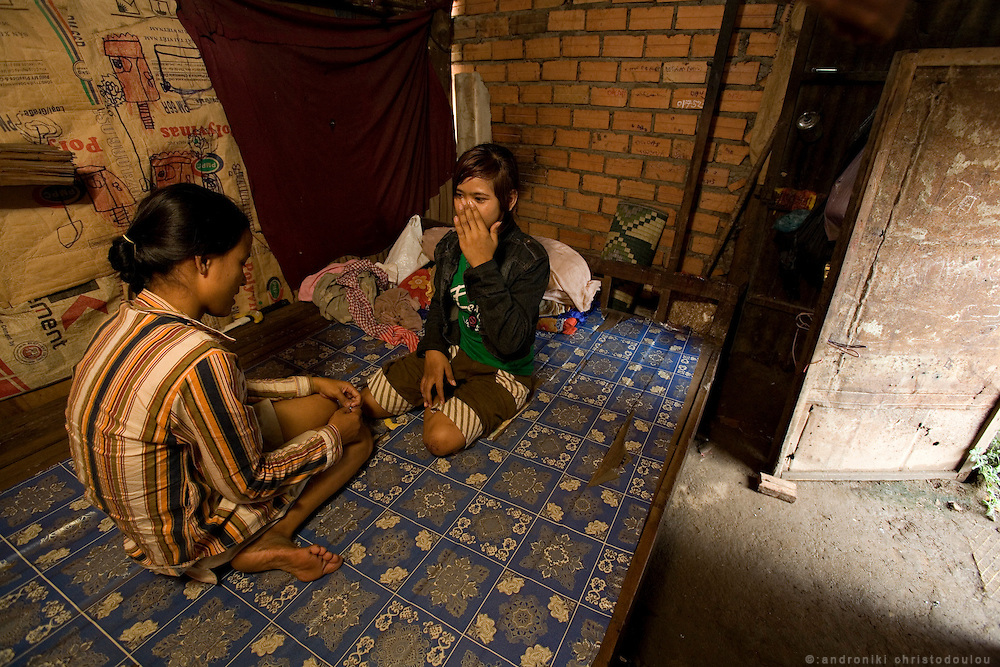 "Son Rathany (14) (R) and Rous Mach (15) (L) who are both working as prostitutes, in the room where they sleep and sometimes bring clients, in a slam behind the ""building"" in Phnom Penh. They both started working as prostitutes about half a year ago. Son after her family broke up and Rous after being tricked to start going to bars by a divorced female friend of hers. They take 1-2 clients a night. Rous goes mainly to ""Martini Pub"" a bar where foreign men go to pick up prostitutes. Son looks very young so it is more difficult for her to go in the bars but she refused to say how she finds customers."