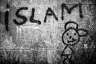 """""""Islam"""" graffiti with a happyt face on the asylum center's wall left by one of its residents. The walls of the center are like an improvised journal of the past and present residents. FEDASIL Rixensart asylum center. Rixensart, Belgium. April 2015. I took these photographs during an international volunteer program that I liderate with an international volunteering group."""