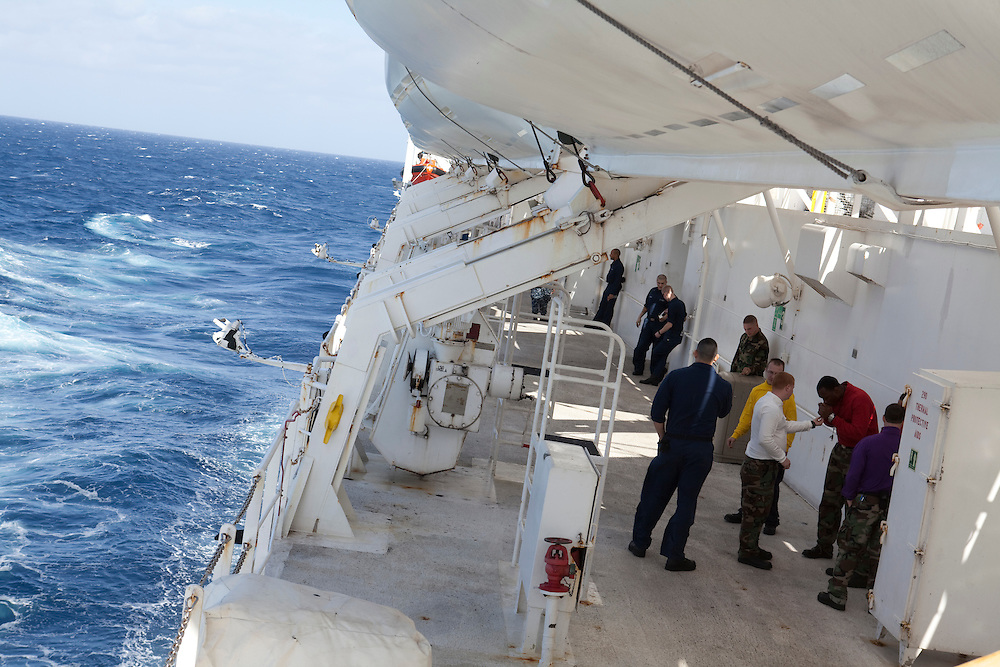 Sailors on board the USNS Comfort, a naval hospital ship, take a smoke break as the ship journeys on its mission to help survivors of the earthquake in Haiti on Monday, January 18, 2010 in the Atlantic Ocean off the coast of the United States.