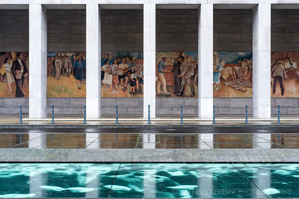 A propaganda mural depicting daily life in a socialist East Germany in Berlin contrasts with an installation of photographs depicting the Nazi occupation of the city on the pavement.