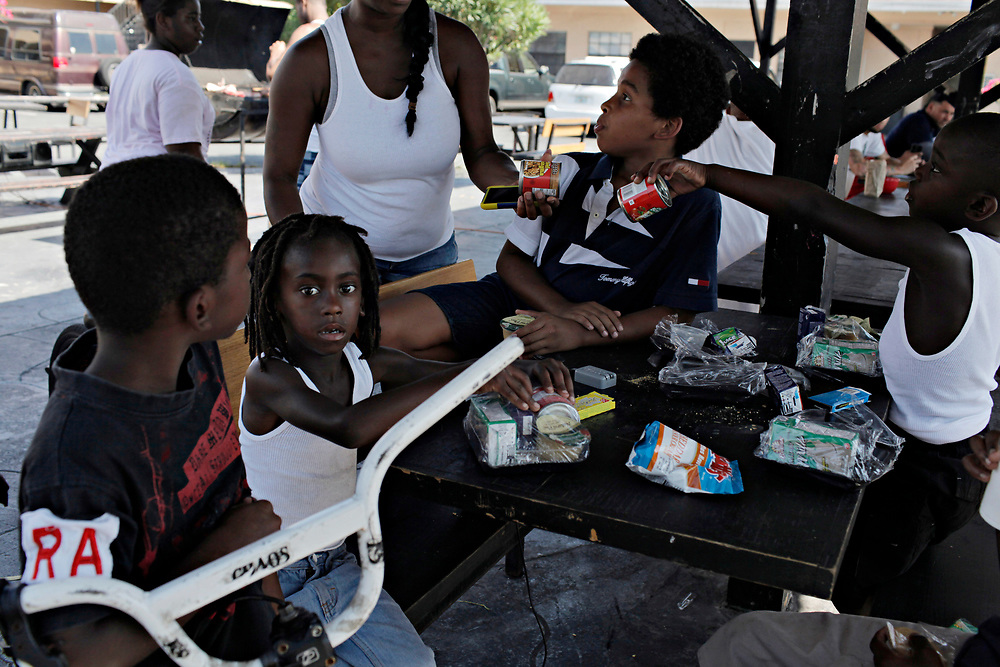 MELISSA LYTTLE | Times<br /> Aaelin Williams, center, and his friends eat their afternoon snacks that are provided to them daily at the Mosley Motel thanks to a volunteer from the Salvation Army.