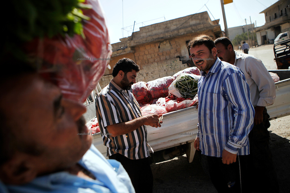 A delivery of fresh paprika has arrived in the morning on the market in Koreen. Vendors and customers negotiate prices and take their goods.<br /> <br /> _ _ _ <br /> <br /> Idlib Interim - Challenging life without central government in the village of Koreen (Idlib Province, Syria)<br /> <br /> Koreen joint the syrian uprisung to ouster president Bashar al-Assad at a very early stage in 2011. It has been scene of Army attacks and heavy shelling since 2012. In the course of the fightings the village of a few thousend inhabitants was almost abandoned as barrel bomb campaings commited by the regime pounded Koreen. But since regime forces retreated to few bases remaining in Idlib province people returned home to establish a new and almost unregulated economic, social and community life. The regimes power has no affect and can&acute;t reach them anymore. On the other hand a new government isn&acute;t established yet and not in sight at all. Koreen is free to make its way.