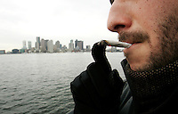 A Boston man demonstrates his marijuana smoking habits for the photographer in a city park.  Photo by Matthew Healey