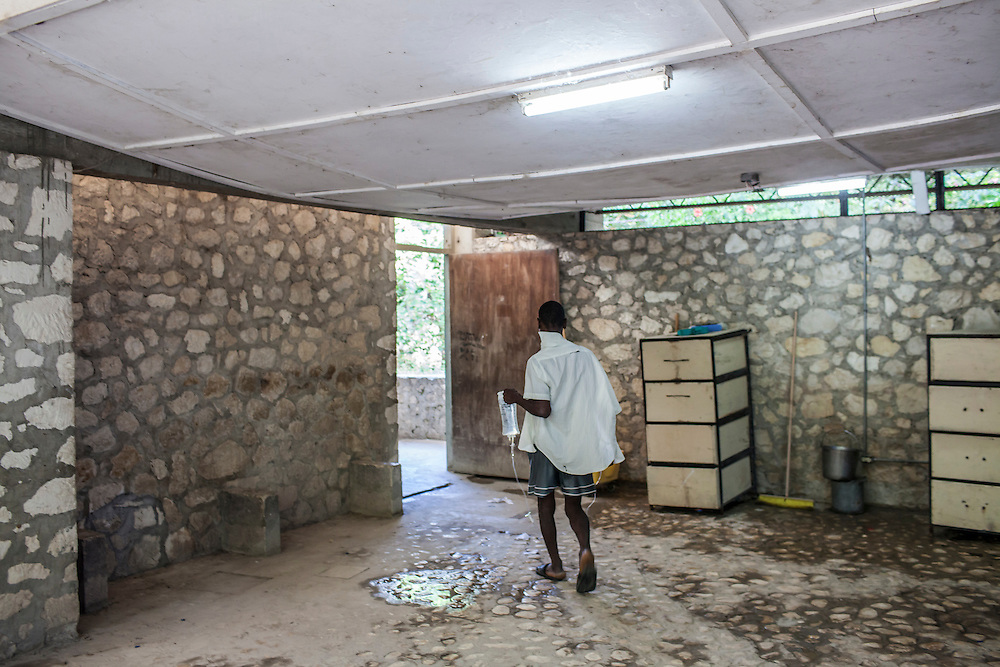 A cholera patient carries his I.V. to the bathroom at the Hospital Albert Schweitzer on Thursday, October 28, 2010 in Deschapelles, Haiti.