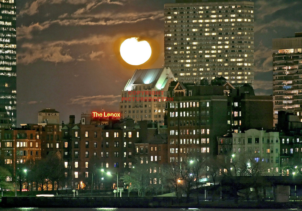 A nearly full yellowish moon (1 day passed) leap frogs over the Boston skyline March 16th 2006.