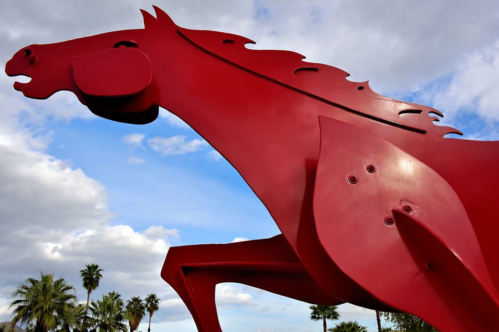 Charger Red Horse Sculpture in Palm Desert, California <br /> Behind the Melissa Morgan Fine Art gallery near the Shops on El Paseo is this giant red horse sculpture. &ldquo;Charger&rdquo; made his first appearance during the 1994 El Paseo Sculpture Exhibition. It later became the symbol for a local restaurant. Although the eatery closed in 2005, the 8 foot high, 16 foot long public art remained on display. Ted Gall created this exciting steel statue.