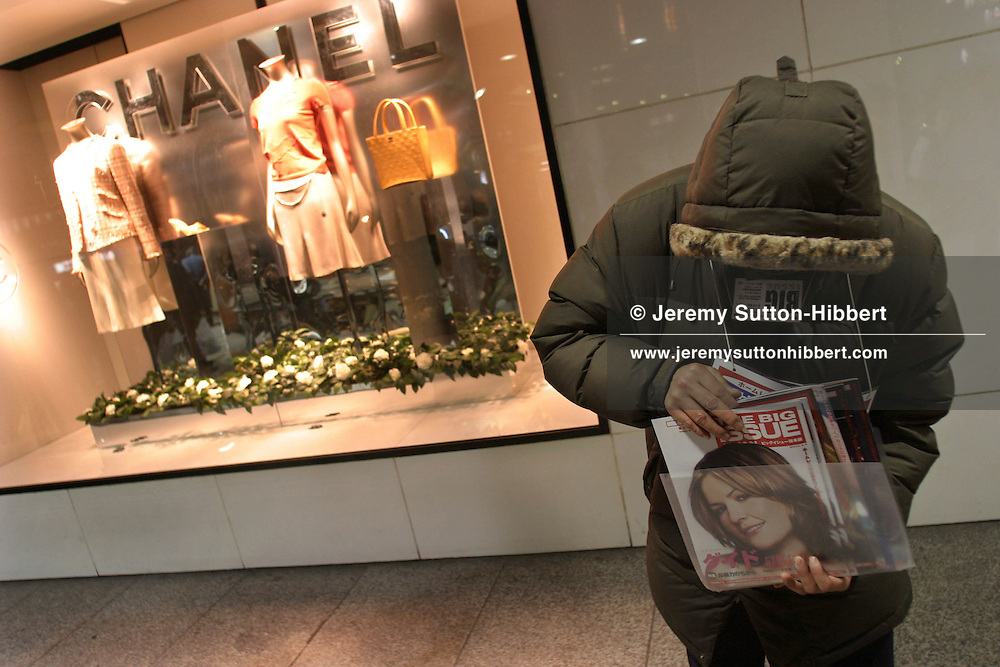 Homeless Japanese man selling 'The Big Issue' magazine, outside a Chanel luxury brand clothing store, in the Shinjuku district of the city, Tokyo, Japan.