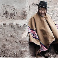 A quechuan man ready for mass on Sunday in the small town of Pisac, Peru wearing a large traditional poncho and woven hat under a sombrero.