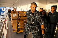 Sailors organize supplies on board the USNS Comfort, a naval hospital ship, before its mission to help survivors of the earthquake in Haiti on Monday, January 18, 2010 in the Atlantic Ocean off the coast of the United States.