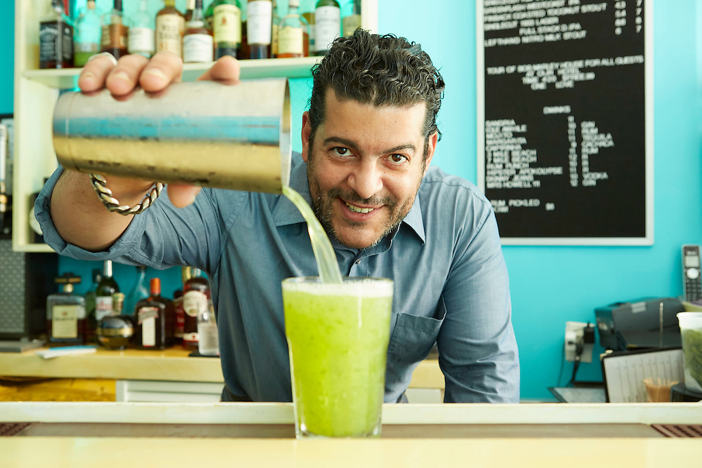 Lifestyle photograph of bartender pouring lime alcoholic drink in bar