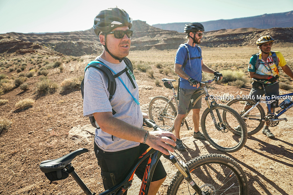 SHOT 10/16/16 3:46:08 PM - Tom Reynolds of Denver, Co. pauses with other riders in the group to take in the view along the White Rim Trail. The White Rim is a mountain biking trip in Canyonlands National Park just outside of Moab, Utah. The White Rim Road is a 71.2-mile-long unpaved four-wheel drive road that traverses the top of the White Rim Sandstone formation below the Island in the Sky mesa of Canyonlands National Park in southern Utah in the United States. The road was constructed in the 1950s by the Atomic Energy Commission to provide access for individual prospectors intent on mining uranium deposits for use in nuclear weapons production during the Cold War. Four-wheel drive vehicles and mountain bikes are the most common modes of transport though horseback riding and hiking are also permitted.<br /> (Photo by Marc Piscotty / &copy; 2016)