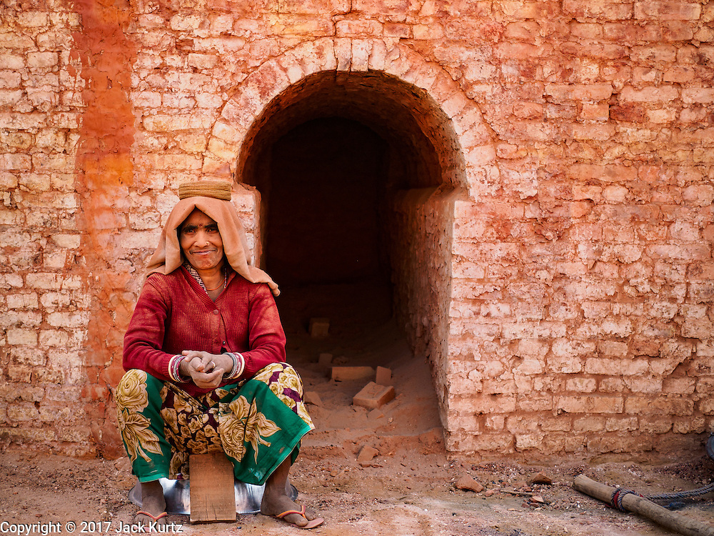 03 MARCH 2017 - BAGMATI, NEPAL: A woman who works at a brick factory in Bagmati, near Bhaktapur, takes a break in the kiln at the factory. There are almost 50 brick factories in the valley near Bagmati. The brick makers are very busy making bricks for the reconstruction of Kathmandu, Bhaktapur and other cities in the Kathmandu valley that were badly damaged by the 2015 Nepal Earthquake. The brick factories have been in the Bagmati area for centuries because the local clay is a popular raw material for the bricks. Most of the workers in the brick factories are migrant workers from southern Nepal.       PHOTO BY JACK KURTZ