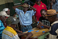 Castries, Saint Lucia: Men play dominoes near the fish market.