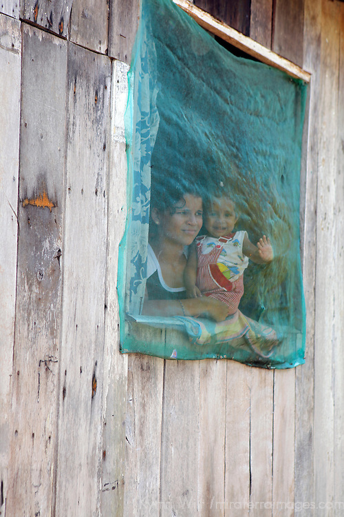 South America, Brazil, Amazon. A young mother peers out with her baby through mosquito screened windows on their Amazon home.