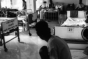 An AIDS patient looks on quietly at a recently vacated bed, his neighbour having died during the night..Wat Prah Bat Nam Phu, Lop Buri, Thailand.September 2003.©David Dare Parker /AsiaWorks Photography