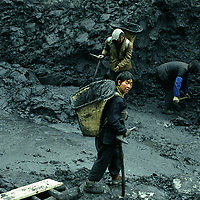 Overground coal is extracted and carried into wicker backets to the refinery.  Men and women carry up to 50kg of coal on their back and they are paid by the amount of buckets.