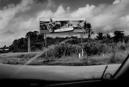 Outdoor advertisement for a chainsaw on the highway out of the capital, Paramaribo that leads into rainforests of Saamaka maroon territory.  Suriname.
