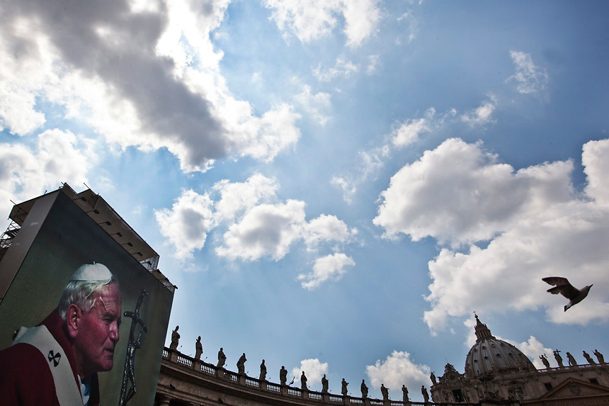 Pilgrims stand in front of a giant image of Pope John Paul II at St. Peter's Square in the Vatican April 29, 2011. As the Vatican prepares to elevate the late pontiff one step closer to sainthood this Sunday, the Catholic world is caught up with beatification fever. Rome is festooned with posters of the former pope on buses and lamp posts as the city where he was bishop for 27 years awaits one of the largest crowds since his funeral in 2005, when millions came to pay tribute
