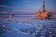 Alaska. Cook Inlet. Oil rig production platforms with sunset on Mt Spurr in the Chigmit Mts.