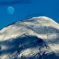 Antarctica, Port Lockroy, Moon sets above glacier-covered summit of mountain peak rising along Antarctic Peninsula