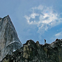 Niels McKibbin near the topout of Paddle Flake on Crescent Spire with the Northeast ridge of Bugaboo Spire behind him, Bugaboo Provincial Park, British Columbia, Canada