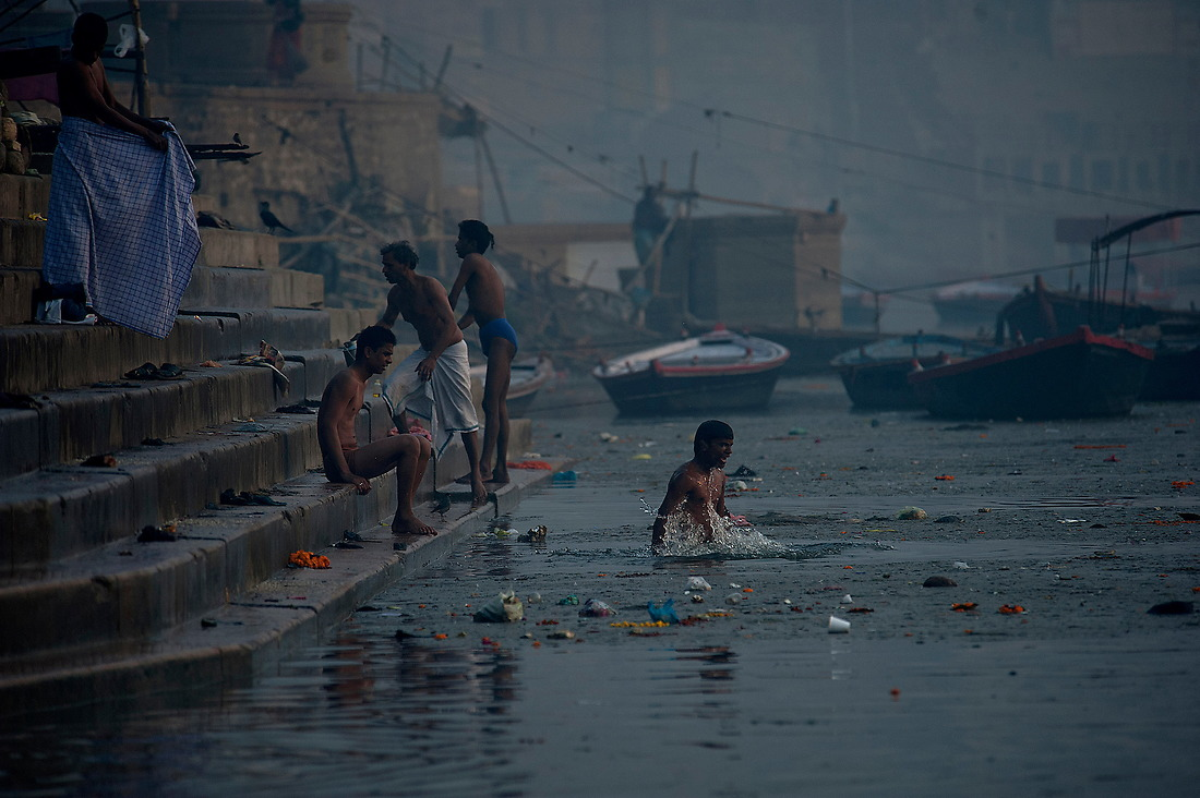 Not bothered by the floating garbage around him, a young man bathes in the rives Ganges from the banks of Varanasi, India on January 31, 2013.Known as the largest river in India with an extraordinary religious importance for Hindus.  It provides water to an estimated 500 million people or more which is larger than any other river in the world. Today, it is sixth most polluted river in the world. — © Jeremy Lock/