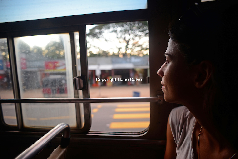 Young woman watches through window in bus, Sri Lanka