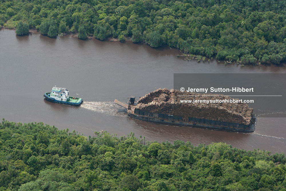 Barge in River Lalang, alongside natural rain forest, and the destruction of it, to make way for Sinar Mas/APP-owned plantations to produce pulp paper, in Rimba Hutan Mas logging concession, in southern Sumatra province, Indonesia, Saturday 16th October 2010.