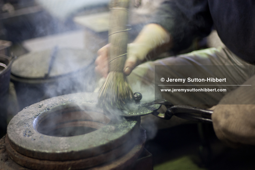 Applying enamel paint using a straw brush to the cast iron teapot lids, and baking the enamel on using heat, at the Iwachu Casting Works in Morioka city, Iwate prefecture, Japan, on Thursday 26th January 2012.