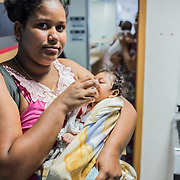 Jayane (17) and her daughter Nathally (6 months) waiting for their turn  at the rehabilitation center FAV (Fundação Atilio Valente) in Recife, Pernambuco. Jayane and her husband Daniel are indigenous people of the tribe Xukuru do Ororubá from the interior of Pernambuco state, 350 km from Recife. They don't have a house in Recife so they have to travel more than three hours in order to come to the rehabilitation center every week