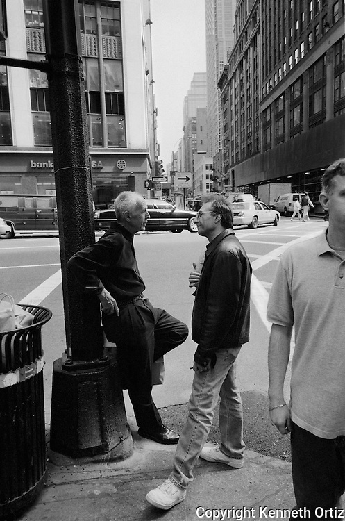 Two men have a conversation on a street corner in Manhattan by the garment district.
