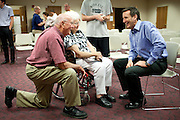 Former Minnesota Gov. Tim Pawlenty talks with Bud McCarville, left, and Mary McCarville, center, after a town hall campaign event in Ft. Dodge, Iowa, July 21, 2011.