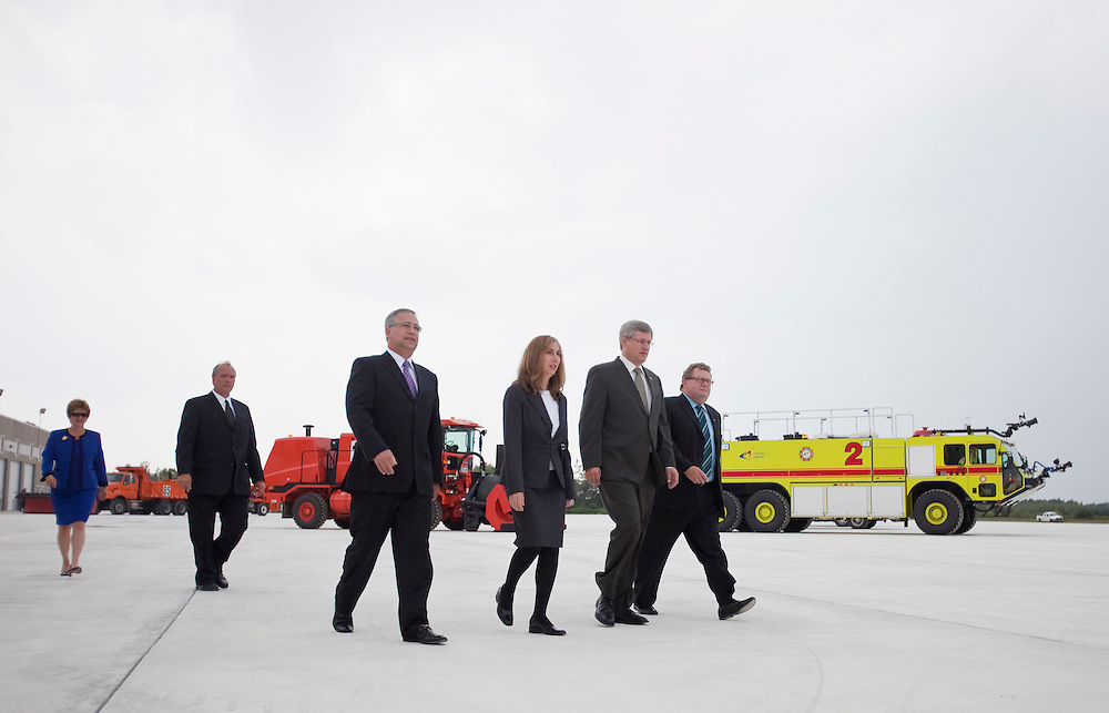 Prime Minister Stephen Harper, 2nd from right, is joined by local officials as he arrives at the opening of the Foreign Trade Cargo Complex at the London International Airport, in London, Ontario, September 2, 2010.<br /> REUTERS/Geoff Robins