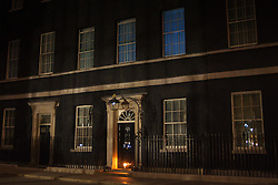 London, August 4th 2014. A single candle illuminates the door of 10 Downing Street as the UK commemorates the centeanary of the outbreak of World War 1.