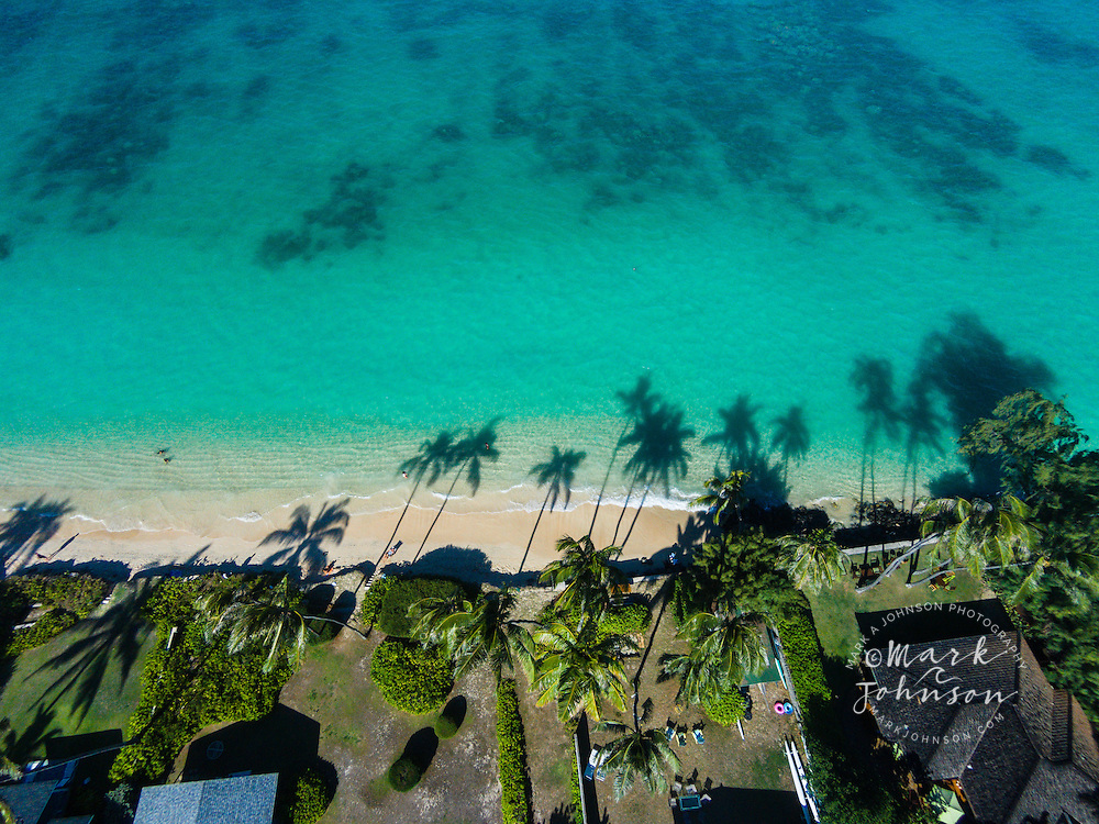 The late afternoon sun casting palm tree shadows onto Lanikai Beach, Oahu, Hawaii