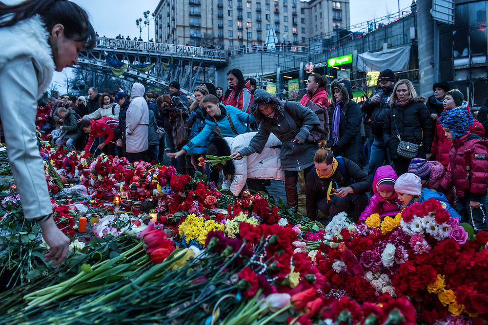 KIEV, UKRAINE - FEBRUARY 23: People lay flowers and pay their respects at a memorial for anti-government protesters killed in clashes with police in Independence Square on February 23, 2014 in Kiev, Ukraine. After a chaotic and violent week, Viktor Yanukovych has been ousted as President as the Ukrainian parliament moves forward with scheduling new elections and establishing a caretaker government. (Photo by Brendan Hoffman/Getty Images)