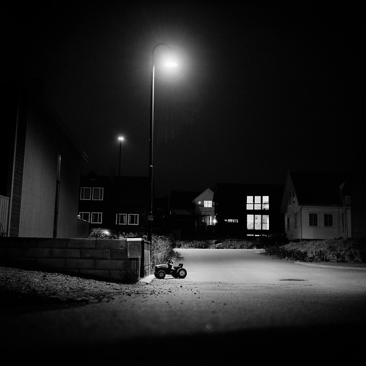 Tractor culture at Jaeren, Rogaland, Norway...Toy tractor parked at night in a quiet neighbourhood at Haalandsmarka, Sola, Norway...Jaeren is one of the major agricultural areas in Norway. There are tractors and traces of tractors almost everywhere. ..Photo by Knut Egil Wang /MOMENT