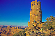 The Watchtower at Desertview, near the Eastern entrance of Grand Canyon NP stands guard on a blue sky day over the top of the canyon rim.