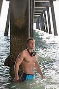 rugged man in a tight bathing suit with a diver's mask under a pier at the ocean