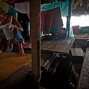 . A mother tends to her child in their makeshift bedroom. The makeshift hallway that leads to their room is nothing more then a string of single planks. Image © Jonah Markowitz/Falcon Photo Agency